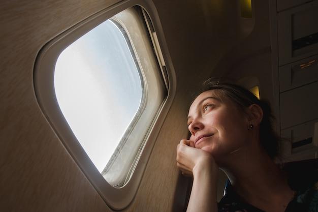 Frau am bullauge im flugzeug