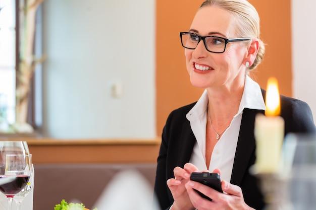 Frau am business-lunch post am telefon überprüfend