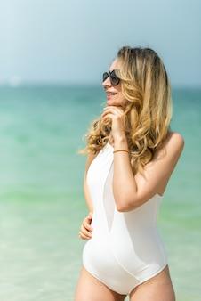 Frau am dubai-strand in den weißen badeanzügen