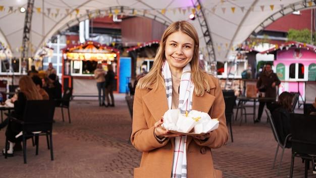 Frau am food court mit foodtrucks die blondine hat sich streetfood gekauft