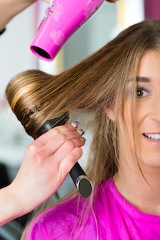 Frau am friseur, die haare getrocknet hat