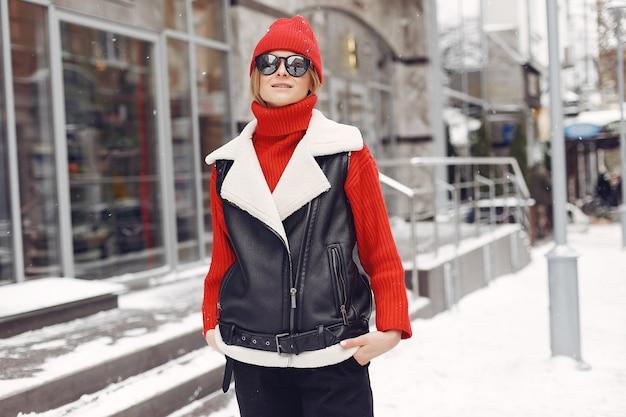 Frau am gebäude. neujahrsstimmung. dame in einer schwarzen jacke.