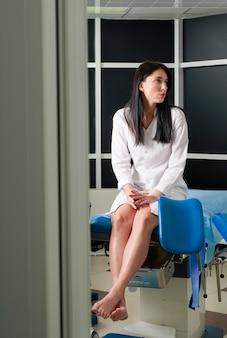 Frau am gynäkologenbüro, das sitzt und auf einen arzt mit testergebnissen wartet, blick durch eine tür