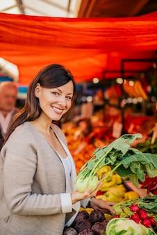 Frau am markt, lebensmittel kaufend.