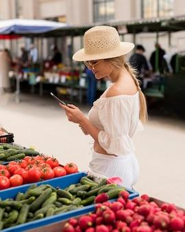 Frau am marktplatz mit ihrem handy