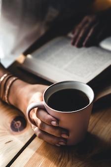 Frau am morgen trinkt kaffee und liest altes buch in einem weißen hemd.