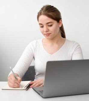 Frau am schreibtisch, die in der tagesordnung schreibt