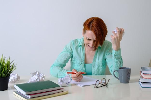 Frau am schreibtisch mit zerknittertem papier ist wütend über ihren ideenmangel frau schriftstellerin ist genervt