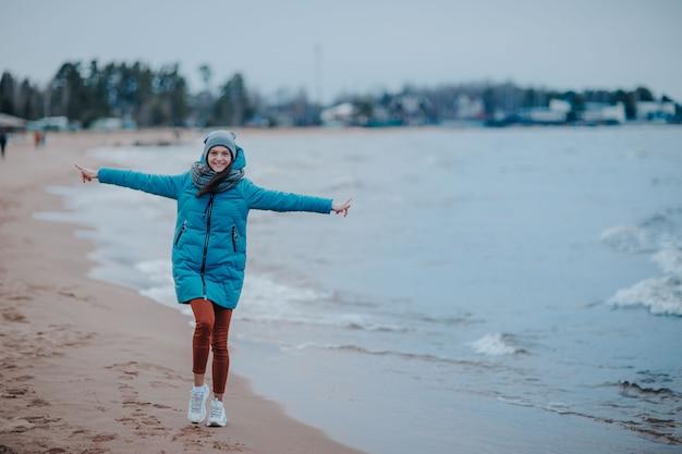 Frau am seeufer im sturm. seeküste mit blauem wasser. wellen an der küste, frau, die am strand geht.