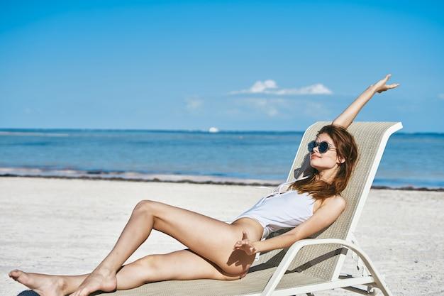 Frau am strand am meer auf einer sonnenliege