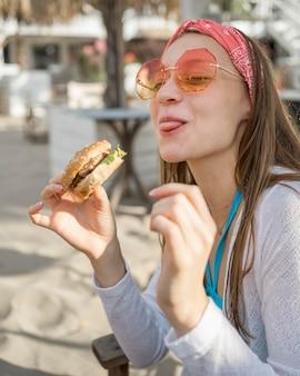 Frau am strand, die einen burger isst