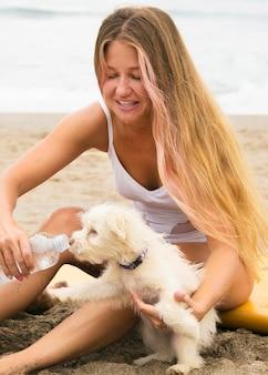 Frau am strand, die hundewasser gibt