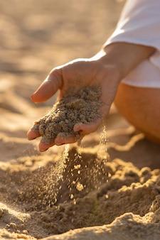 Frau am strand, die sand in ihrer hand hält