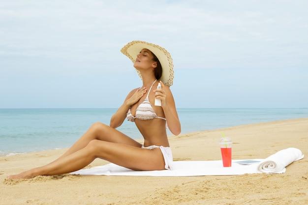Frau am strand, die sonnenschutzspray auf ihren körper anwendet