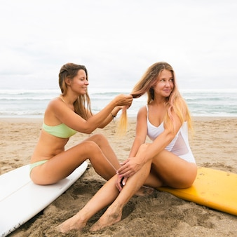 Frau am strand flechtet die haare ihres freundes