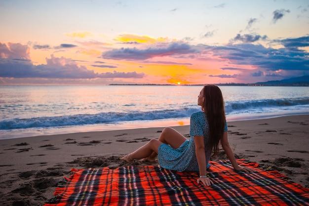 Frau am strand genießt sommerferien mit blick auf das meer