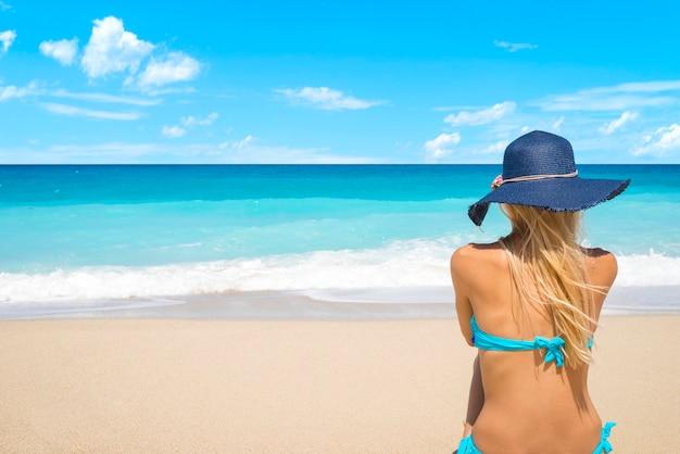 Frau am strand mit blick auf das meer, das sommerferien genießt