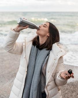 Frau am strand mit einem getränk aus der flasche
