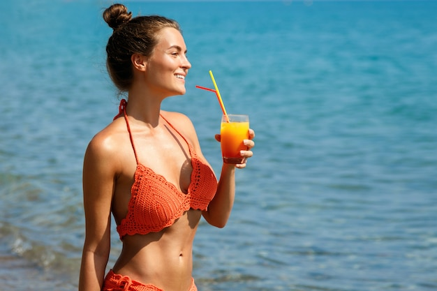 Frau am strand mit einem glas cocktail