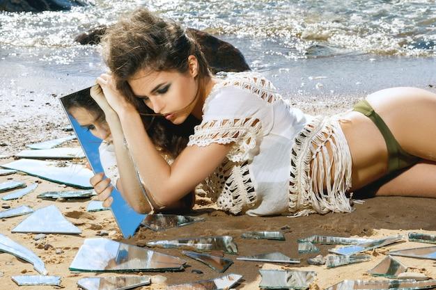 Frau am strand mit einem scherben von spiegel