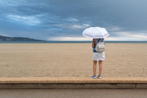 Frau am strand mit regenschirm