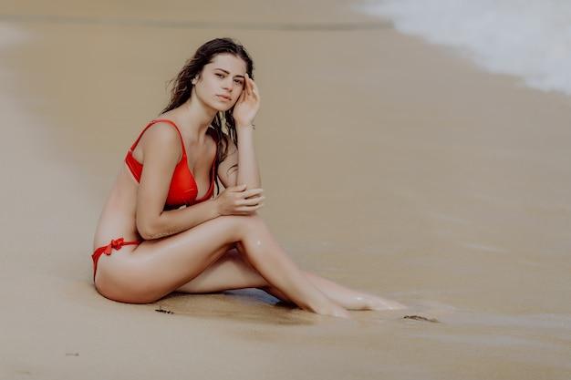 Frau am strand sitzt im sand, der ozean betrachtet, der sonne und sommerurlaubsferienurlaub genießt.