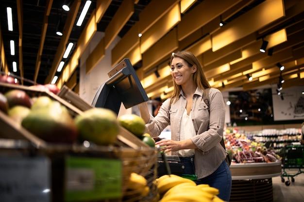 Frau am supermarkt, der selbstbedienungs-digitalwaage verwendet, um das gewicht von obst zu messen