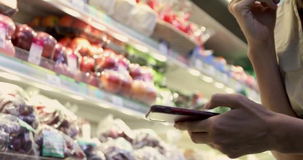 Frau am supermarkt unter verwendung der smartphone-nahaufnahme