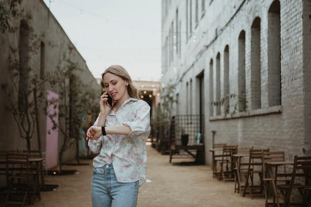 Frau am telefon, die die straße entlang geht und auf die zeit schaut