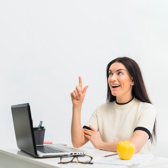 Frau am tisch, die finger oben zeigt