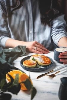 Frau am tisch mit einem schönen und leckeren frühstück. hüttenkäsepfannkuchen auf einem teller, tasse mit kaffee und orangen auf einem weißen hölzernen hintergrund.