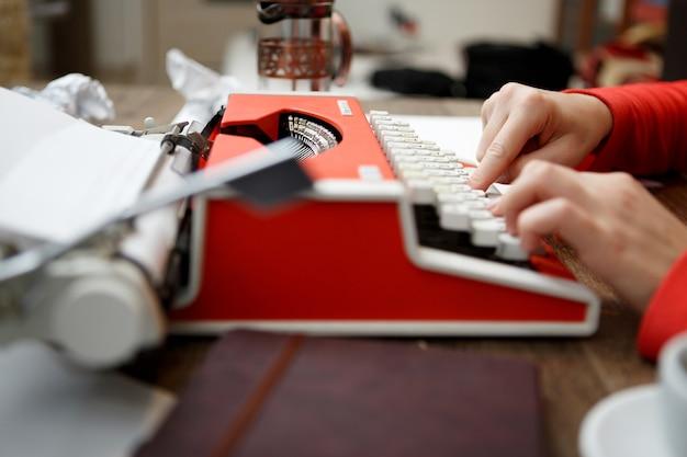 Frau am tisch tippt auf schreibmaschine