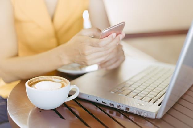 Frau am trinkenden kaffee des cafés und am gebrauchshandy für geschäft.