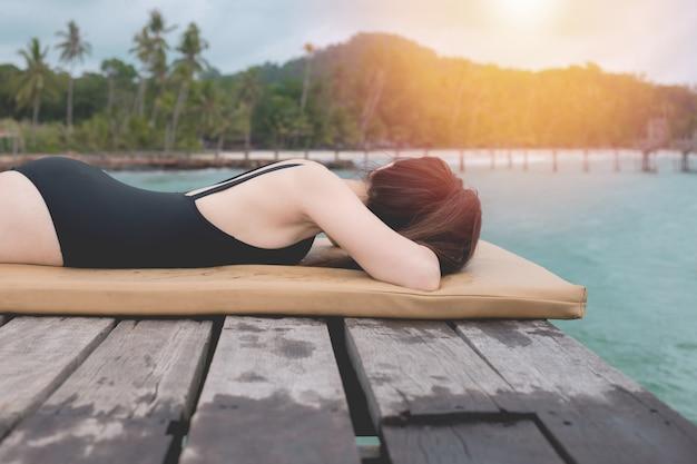 Frau am tropischen strand, junge asiatische frau liegend auf holz pier strand.