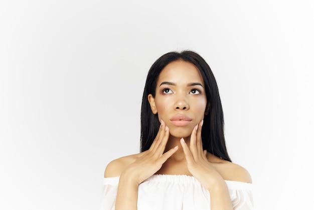 Frau amerikanisches aussehen frisur kosmetik heller hintergrund. foto in hoher qualität