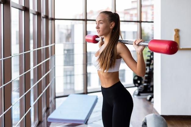 Frau an anhebender gewichtsstange der turnhalle