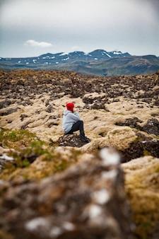 Frau an bemoosten steinen in island