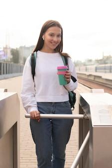 Frau an den drehkreuzen, die eine bunte kaffeetasse halten