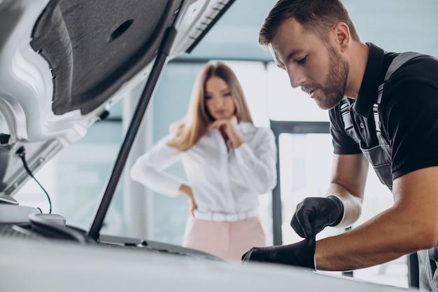 Frau an der acr-tankstelle, die ihr auto mit einem mechaniker überprüft Kostenlose Fotos