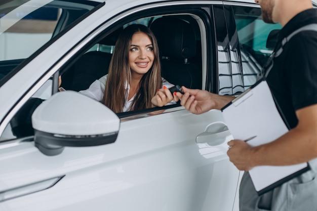 Frau an der acr-tankstelle, die ihr auto mit einem mechaniker überprüft