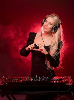 Frau an der dj-konsole, die herzform zeigt