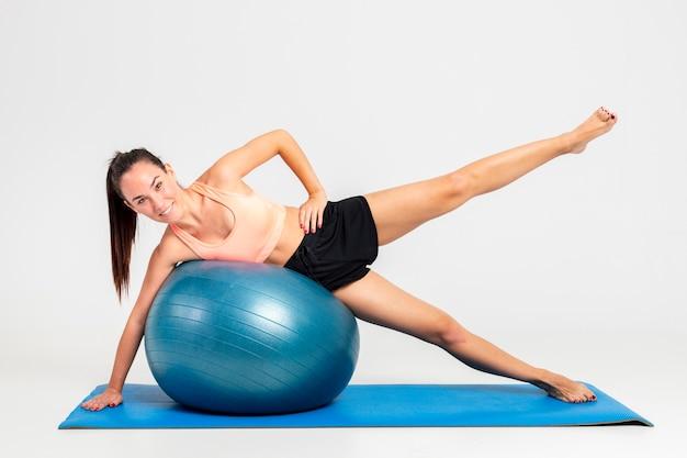 Frau an der gymnastik auf matte mit aufprallendem balltraining