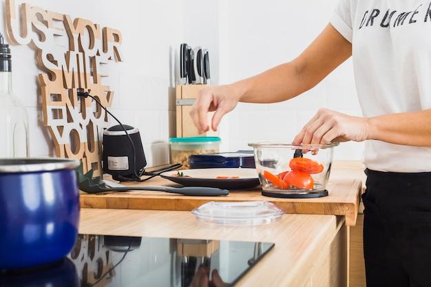 Frau an der küche, die tomaten in mischmaschine einsetzt
