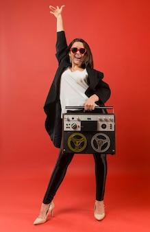Frau an der partei, die sonnenbrille mit radio trägt