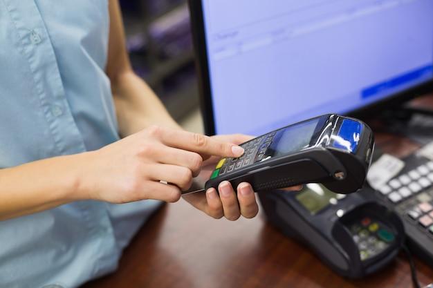 Frau an der registrierkasse, die mit kreditkarte zahlt