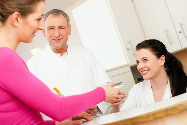 Frau an der rezeption der klinik