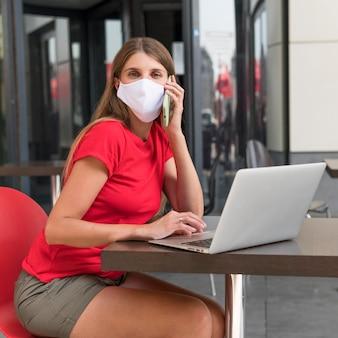 Frau an der terrasse mit gesichtsmaske