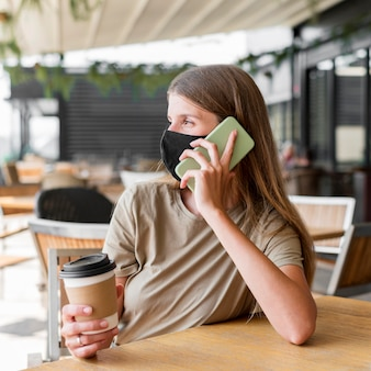 Frau an der terrasse mit maske, die auf handy spricht
