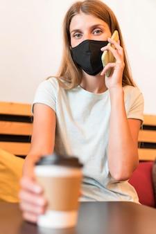 Frau an der terrasse mit maske