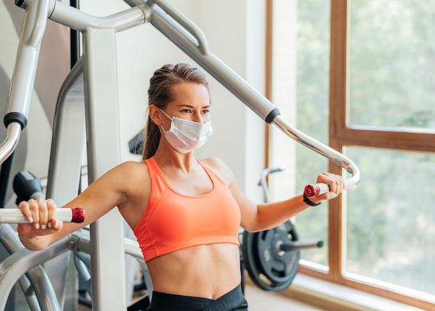 Frau an der turnhalle, die übungen mit medizinischer maske tut